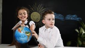 μαύρο σχολείο έννοιας βιβλίων ανασκόπησης copyspace Το Schoolkids κάθεται σε ένα παιχνίδι γραφείων με μια σφαίρα σε το Τα παιδιά  φιλμ μικρού μήκους
