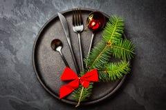 Μαύρο σύνολο μαχαιροπήρουνων, διακόσμηση Χριστουγέννων στο πιάτο σιδήρου, υπόβαθρο πλακών Στοκ Εικόνες