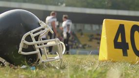 Μαύρο τιμόνι ποδοσφαίρου που βρίσκεται στην πίσσα, παίκτες που επικοινωνεί πριν από τη σημαντική αντιστοιχία φιλμ μικρού μήκους