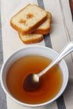 Μαύρο τσάι με τη ζάχαρη και κέικ με τη μαρμελάδα σε μια πετσέτα Στοκ Φωτογραφίες