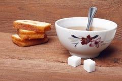 Μαύρο τσάι με τη ζάχαρη και κέικ με τη μαρμελάδα στο ξύλινο υπόβαθρο Στοκ εικόνα με δικαίωμα ελεύθερης χρήσης