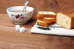 Μαύρο τσάι με τη ζάχαρη και κέικ με τη μαρμελάδα στο ξύλινο υπόβαθρο Στοκ Εικόνα