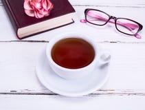 Μαύρο τσάι σε ένα λευκό γύρω από το φλυτζάνι με ένα πιατάκι Στοκ Εικόνες