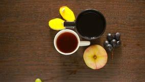 Μαύρο τσάι στις κούπες lunch πίνακας με ένα ποτό και ένα επιδόρπιο επάνω από την όψη φιλμ μικρού μήκους