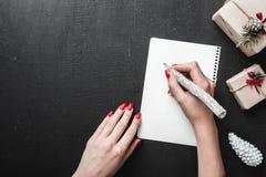 Μαύρο υπόβαθρο με τα σύγχρονα δώρα με μια κυρία που γράφει Στοκ εικόνα με δικαίωμα ελεύθερης χρήσης