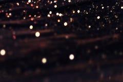 Μαύρο υπόβαθρο με τα φω'τα σπινθηρίσματος Αφηρημένη σκοτεινή σύσταση W Στοκ Φωτογραφίες