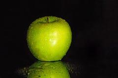Μαύρο υπόβαθρο με την υγρή πράσινη Apple Στοκ Εικόνα