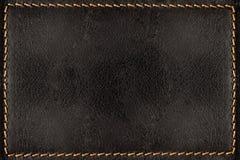 Μαύρο υπόβαθρο σύστασης δέρματος με τις πορτοκαλιές ραφές Στοκ φωτογραφία με δικαίωμα ελεύθερης χρήσης