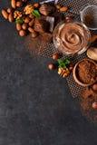 Μαύρο υπόβαθρο τροφίμων με το κακάο, τα καρύδια και τη σοκολάτα στοκ φωτογραφίες