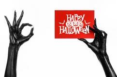 Μαύρο χέρι του θανάτου που κρατά μια κάρτα εγγράφου με τις λέξεις ευτυχείς αποκριές Στοκ Εικόνες
