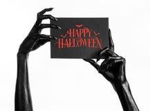 Μαύρο χέρι του θανάτου που κρατά μια κάρτα εγγράφου με τις λέξεις ευτυχείς αποκριές Στοκ φωτογραφία με δικαίωμα ελεύθερης χρήσης