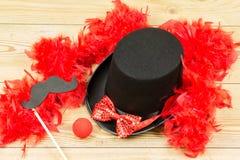 Μαύρο ψηλό καπέλο, κόκκινο χνουδωτό boa φτερών, κόκκινος δεσμός τόξων και κόκκινο clow Στοκ Φωτογραφίες