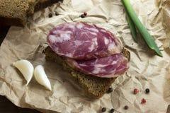 Μαύρο ψωμί με το τεμαχισμένο λουκάνικο Στοκ Εικόνες