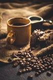Μαύρο Arabica καφέ στο καφετί υπόβαθρο σάκων γυαλιού και γάλακτος και επιδορπίων στην περιοχή χαμηλού φωτός Στοκ εικόνες με δικαίωμα ελεύθερης χρήσης