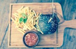Μαύρο burger με τις τηγανιτές πατάτες σε ένα ξύλινο πιάτο Στοκ εικόνα με δικαίωμα ελεύθερης χρήσης