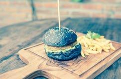 Μαύρο burger με τις τηγανιτές πατάτες σε ένα ξύλινο πιάτο Στοκ εικόνες με δικαίωμα ελεύθερης χρήσης
