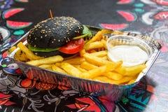 Μαύρο burger με τις τηγανιτές πατάτες Στοκ Εικόνες