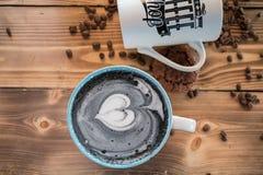 Μαύρο latte με το μαύρο αφρό καρδιών στο κεραμικό φλυτζάνι τέχνης στον παλαιό ξύλινο πίνακα, τοπ άποψη Στοκ Εικόνες
