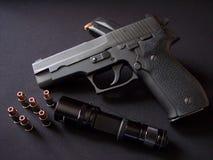 Μαύρο 9mm ημιαυτόματο περίστροφο πιστολιών με τα πυρομαχικά και το φακό στοκ φωτογραφία