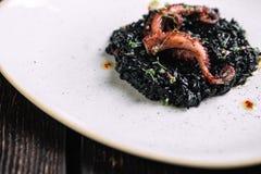Μαύρο risotto με τα πλοκάμια μελανιού και χταποδιών σουπιών στο ανώμαλο πιάτο μορφής Στοκ φωτογραφίες με δικαίωμα ελεύθερης χρήσης