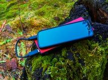 Μαύρο smartphone και κόκκινο powerbank στοκ εικόνα με δικαίωμα ελεύθερης χρήσης