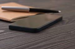 Μαύρο smartphone στον εργασιακό χώρο γραφείων με το σημειωματάριο στοκ εικόνα
