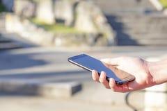 Μαύρο smartphone υπό εξέταση στο πάρκο υπαίθρια, αναμμένο από τον ήλιο στοκ εικόνες