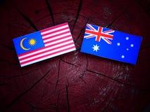 Μαλαισιανή σημαία με την αυστραλιανή σημαία σε ένα κολόβωμα δέντρων που απομονώνεται Στοκ Φωτογραφίες