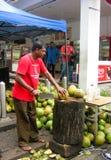 Μαλαισιανό άτομο που κόβει τις νέες καρύδες Στοκ Φωτογραφία