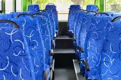 Μαλακά καθίσματα για τους επιβάτες μέσα στην αίθουσα του κενού λεωφορείου πόλεων Στοκ Εικόνες