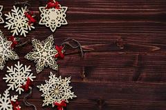 Μαλακά μπεζ ξύλινα snowflakes Χριστουγέννων σε ένα εκλεκτής ποιότητας ξύλινο καφετί υπόβαθρο Στοκ φωτογραφίες με δικαίωμα ελεύθερης χρήσης
