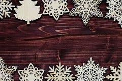 Μαλακά μπεζ ξύλινα snowflakes Χριστουγέννων σε ένα εκλεκτής ποιότητας ξύλινο καφετί υπόβαθρο Στοκ εικόνα με δικαίωμα ελεύθερης χρήσης