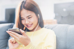 Μαλακή εστίαση του έξυπνου τηλεφώνου στο χέρι γυναικών χρησιμοποιείται να ακούσει τη μουσική ευτυχώς Σε μια εποχή της χαλάρωσης μ Στοκ εικόνα με δικαίωμα ελεύθερης χρήσης