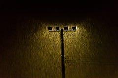 Μαλακός πυροβολισμός των φω'των λαμπτήρων οδών νύχτας στη δυνατή βροχή Στοκ Εικόνες