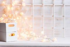 Μαλακό εγχώριο ντεκόρ Χριστουγέννων με το κάψιμο φω'των και κιβώτια σε ένα άσπρο ξύλινο υπόβαθρο Στοκ Φωτογραφίες
