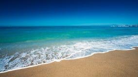 Μαλακό πλύσιμο κυμάτων θάλασσας ωκεάνιο πέρα από τη χρυσή άμμο Στοκ Εικόνες