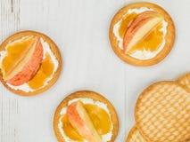 Μαλακό τυρί Ricotta με τη φρέσκια τεμαχισμένη Apple και μέλι σε ένα μπισκότο ή μια κροτίδα Στοκ Εικόνες