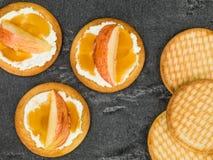 Μαλακό τυρί Ricotta με τη φρέσκια τεμαχισμένη Apple και μέλι σε ένα μπισκότο ή μια κροτίδα Στοκ εικόνες με δικαίωμα ελεύθερης χρήσης
