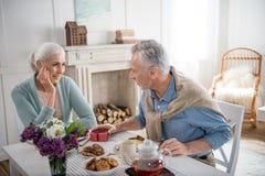 Μαλλιαρό άτομο που παρουσιάζει το δώρο στη σύζυγό του κατά τη διάρκεια του προγεύματος Στοκ Εικόνα