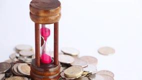 Μείωση άμμου μέσω του βολβού των νομισμάτων κλεψυδρών και ξένου νομίσματος στο υπόβαθρο απόθεμα βίντεο