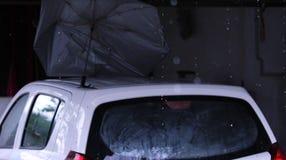 Μείωση βροχής από τη στέγη με το αυτοκίνητο & την ομπρέλα κάτω από το υπόστεγο Στοκ Εικόνες