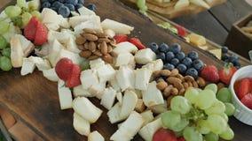 Μεγάλα ανάμεικτα φυσικά και υγιή οργανικά παρμεζάνα γκούντα Cheder τυριών και μούρα και καρύδια φρούτων για τη γιορτή των νεολαιώ φιλμ μικρού μήκους