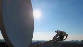 Μεγάλα δορυφορικά πιάτα στη στέγη σπιτιών που πιάνει τα ραδιο κύματα, βιομηχανία τεχνολογίας απόθεμα βίντεο