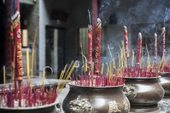 Μεγάλα κόκκινα ραβδιά θυμιάματος με τους κινεζικούς χαρακτήρες σε τους στα δοχεία χαλκού σε έναν βουδιστικό ναό στη πόλη Χο Τσι Μ στοκ φωτογραφία με δικαίωμα ελεύθερης χρήσης
