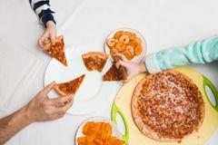 Μεγάλα οικογενειακά χέρια που παίρνουν την πίτσα από το πιάτο Στοκ φωτογραφία με δικαίωμα ελεύθερης χρήσης