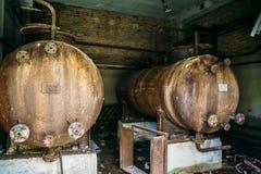 Μεγάλα σκουριασμένα βαρέλια σιδήρου σε ένα εγκαταλειμμένο εργοστάσιο εγκαταλειμμένος βιομηχανικός Στοκ εικόνα με δικαίωμα ελεύθερης χρήσης