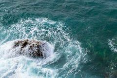μεγάλα σπάζοντας κύματα α&k Κύματα και άσπρος αφρός Παράκτιες πέτρες επάνω από την όψη Το θαλάσσιο υπόβαθρο είναι πράσινο Στοκ Φωτογραφία