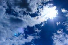 Μεγάλα χνουδωτά σύννεφα υψηλά στον ουρανό Ο ήλιος λάμπει μέσω των σύννεφων Στοκ Φωτογραφία