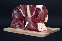 Μεγάλα χοντρά κομμάτια του streaky κρέατος βόειου κρέατος για την ακατέργαστη σίτιση των γατών και των σκυλιών στον ξύλινο πίνακα στοκ φωτογραφία με δικαίωμα ελεύθερης χρήσης
