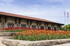 Μεγάλα flowerbeds των πορτοκαλιών και κόκκινων τουλιπών με το υποστήριγμα-βασιλικό σαλέ στο υπόβαθρο στοκ φωτογραφίες